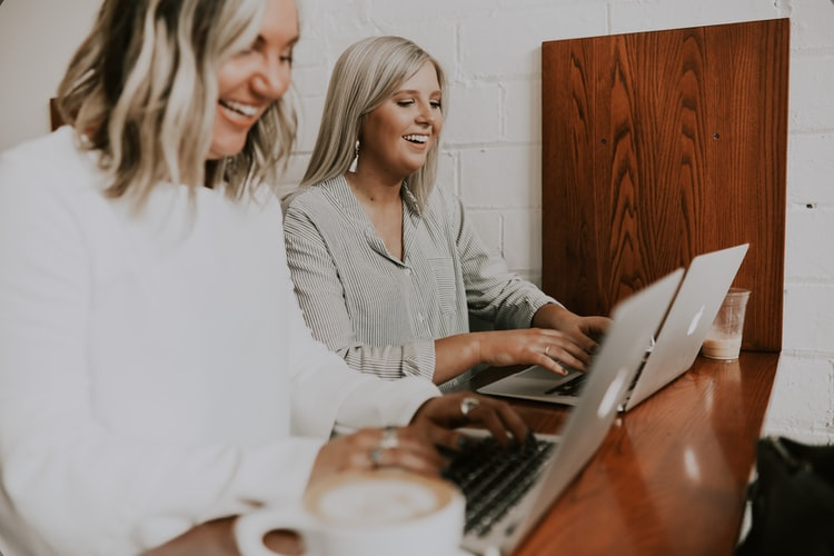 two-women-smiling-at-a-desk-while-working